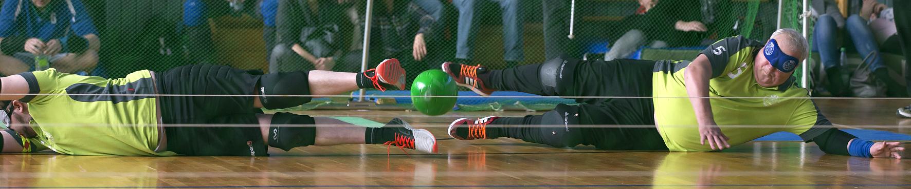 Spielszene Torball: zwei Spieler in der Abwehrhaltung mit den Füßen zueinander. Der Ball kommt genau auf die Schnittstelle.