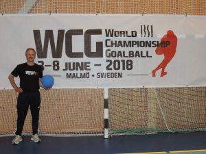Alexander Knecht mit einem Goalball in der Hand vor dem Banner für die Goalball WM in Malmö (Schweden)