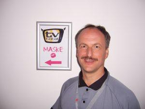 Alexander Knecht neben einem Hinweisschild, wo es zur Maske für TV-Total geht
